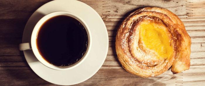 Caffè Americano neben einem Teilchen