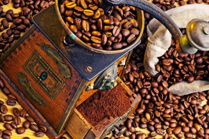 Viele Kaffeebohnen liegen neben einer Kaffeemühle. Frisch gemahlener Kaffee