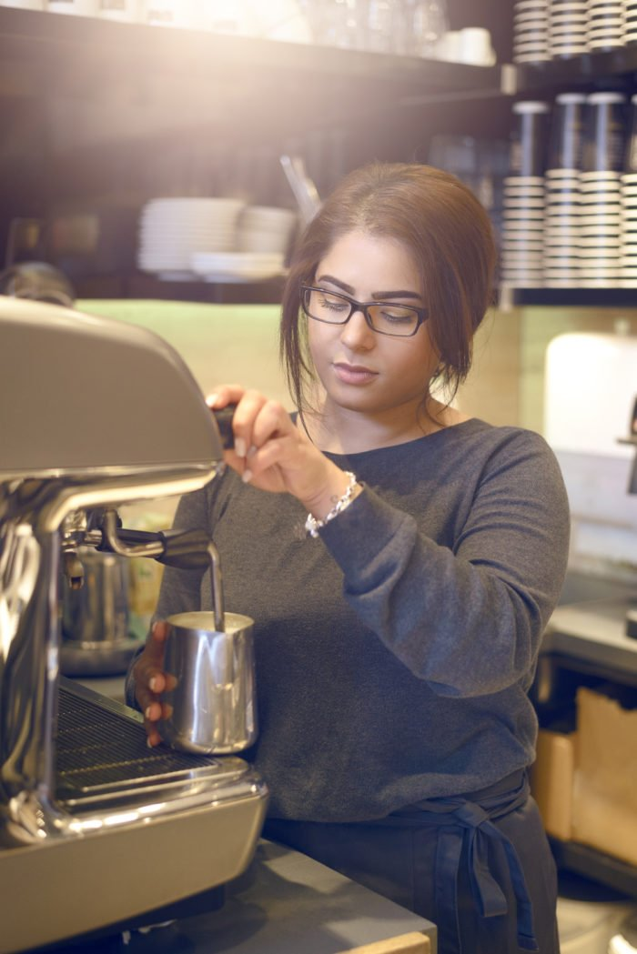 Female barista or waitress making a cup of cappuccino in a coffee house or cafeteria pouring the hot frothy milk into the coffee cup