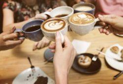 gruppe von leuten stößt mit kaffeetassen an latte art