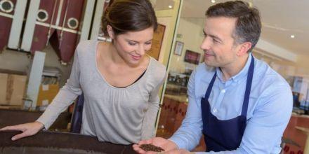 Barista zeigt Frau Unterschied zwischen Kaffeebohnen Röstverfahren
