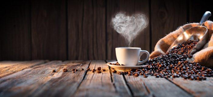 Kaffeetasse dampf herz neben kaffeebohnen