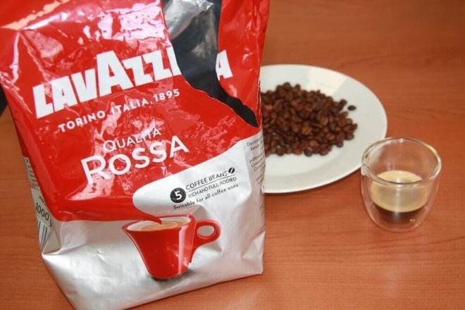 Qualita Rossa von Lavazza Kaffeeverpackung offen mit Kaffeebohnen auf Teller und Kaffee