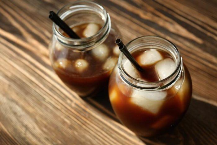 Kalter Kaffee im Glas mit Eiswürfeln und Strohhalm