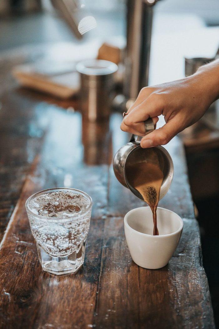 Barista-gießt-Kaffee-in-Tasse-Wasserglas