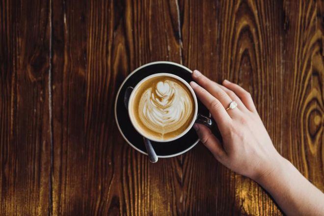 Latte-Art-Frau-hält-Tasse