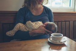 Stillzeit-mama-stillt-baby-kaffeetasse-auf-tisch