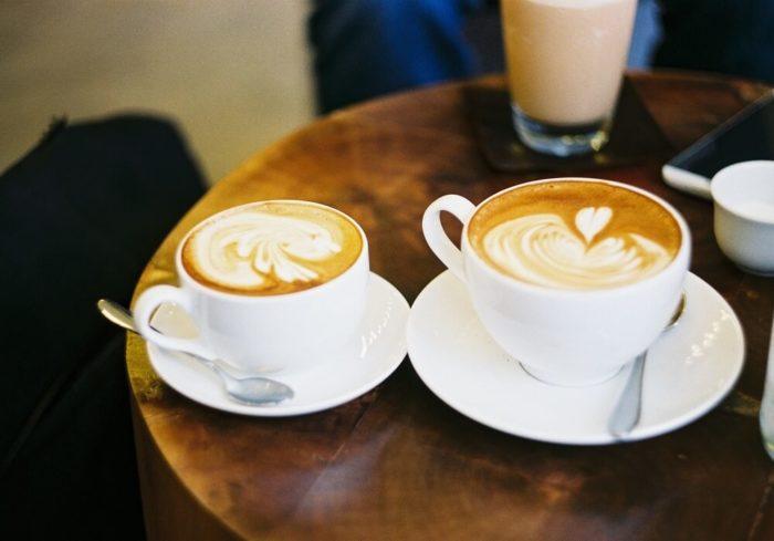 zwei-kaffeetassen-auf-tisch-latte-art-herz