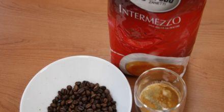Segafredo Intermezzo Verpackung neben Bohnen und frisch zubereitetem Kaffee