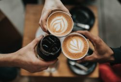 Drei Personen stoßen mit Kaffee an