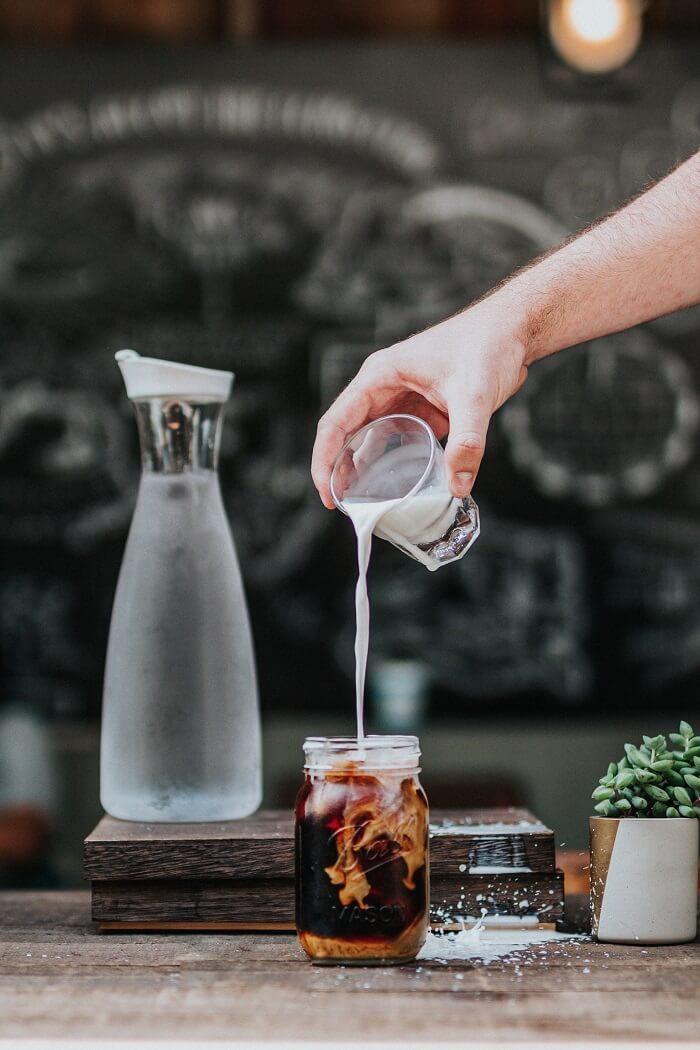 Milch wird in Kaffee gegossen