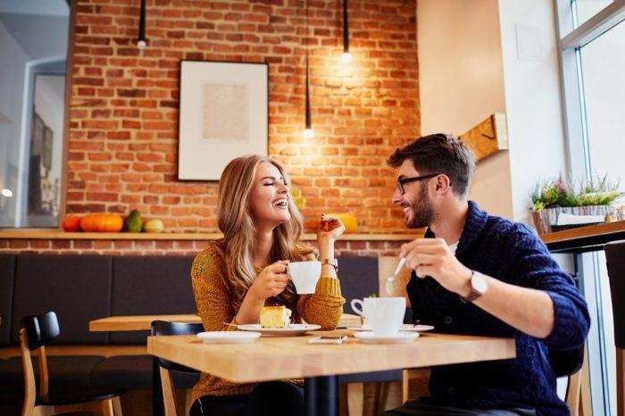 Mann und Frau lachend bei Kaffee und Kuchen