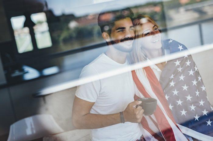 Frau in USA Flagge lehnt neben Mann mit Kaffeetasse