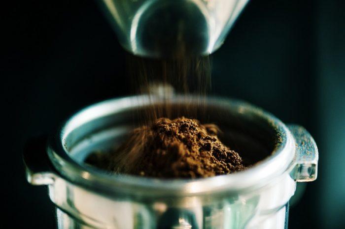 Gemahlener Kaffee wird in Siebtraeger geschuettet