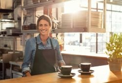 Frau serviert Cappuccino