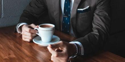 Mann im Anzug hält Kaffee in der Hand