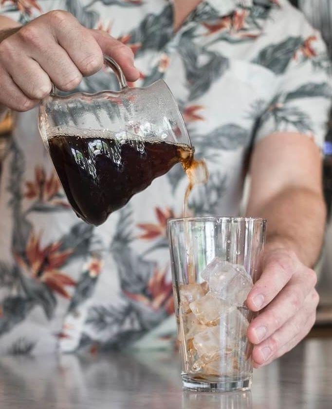 Cold Brew Kaffee wird in Glas mit Eiswürfeln gegossen