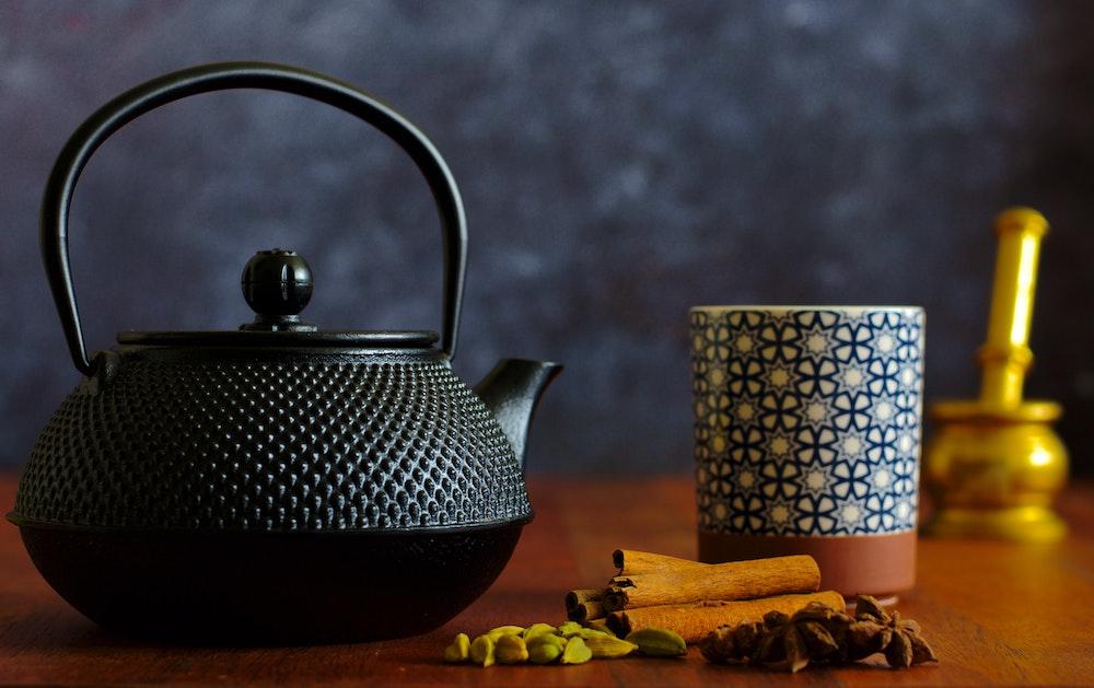 Chai Latte serviert in Teekanne mit Gewürzen