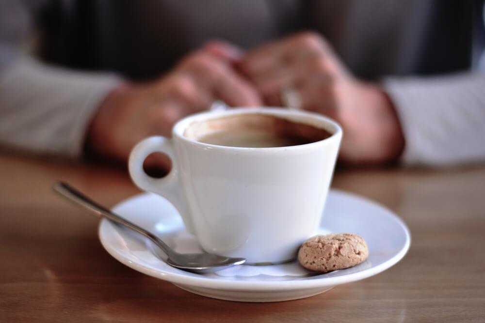 Kaffee auf weißem Porzellan mit Amarettini