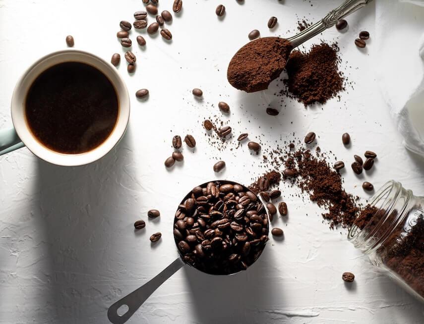 frisches Kaffeemehl neben Kaffeebohnen und Kaffee in Tasse