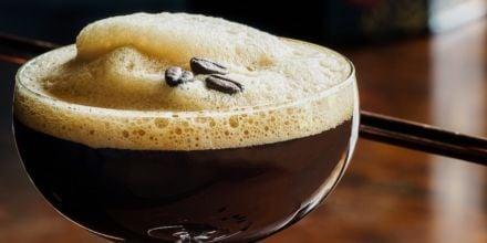 Espresso Martini in Glas mit Espressobohnen auf Schaum quer