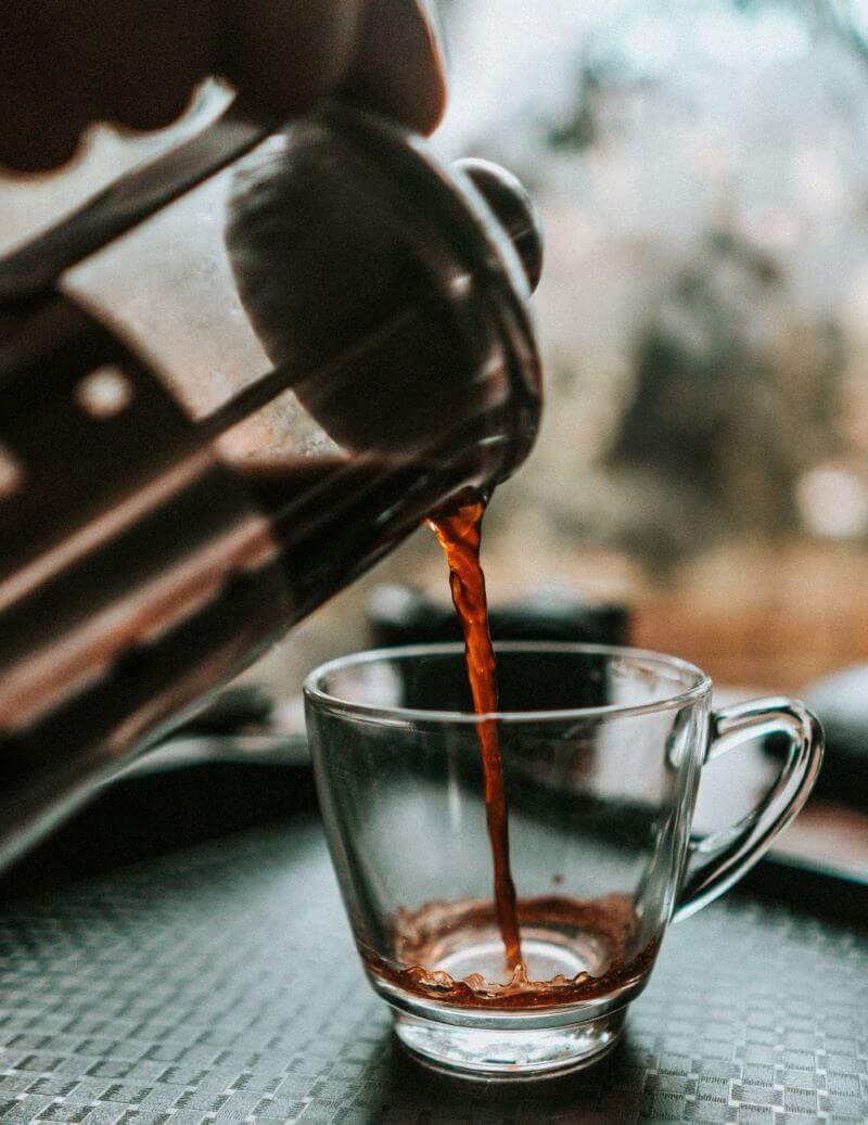 French Press Kaffee wird in Glastasse gegossen