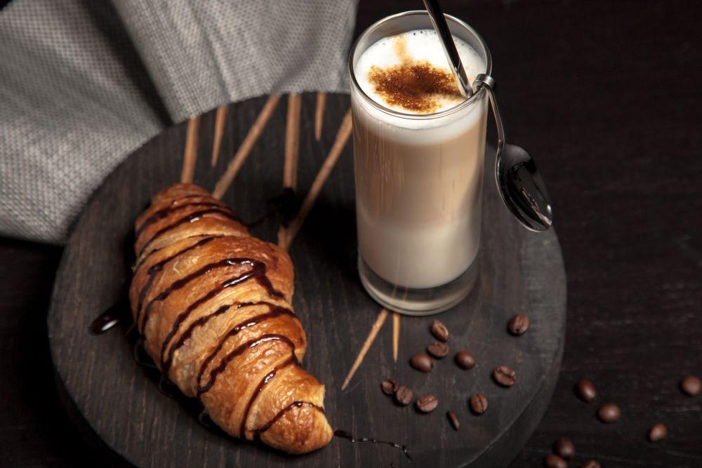 Latte Macchiato neben Croissant
